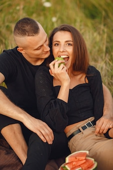 Couple in a field. woman in a black blouse.  people with watermelon.