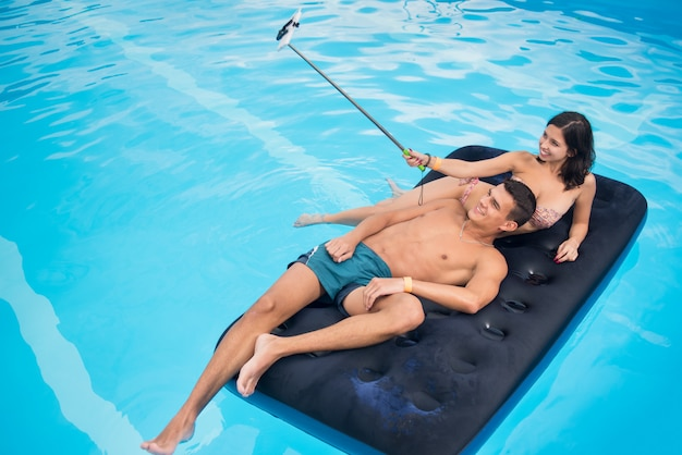 Couple floating on mattress in pool