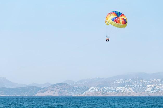 Пара, летящая на разноцветном парашюте, висит в воздухе