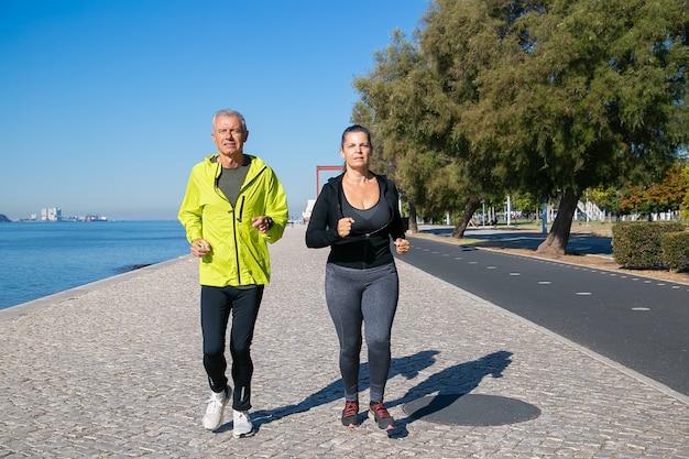Coppia di appassionati di jogging maturi concentrati che corre lungo la riva del fiume. uomo dai capelli grigi e donna che indossa abiti sportivi, correndo all'esterno. attività e concetto di pensionamento