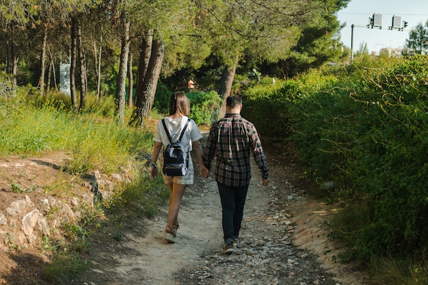 Couple in a forest, they are walking hand in hand