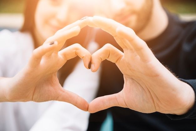 Couple forming heart with hands
