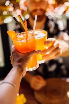 カフェで晴れた日においしいトロピカルカクテルのグラスをチリンと鳴らすカップルの友人