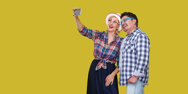 Couple of friends, cute adult man and woman in casual checkered shirt standing together and making selfie foto for memory or video call, toothy smile. indoor, isolated, studio shot, yellow background