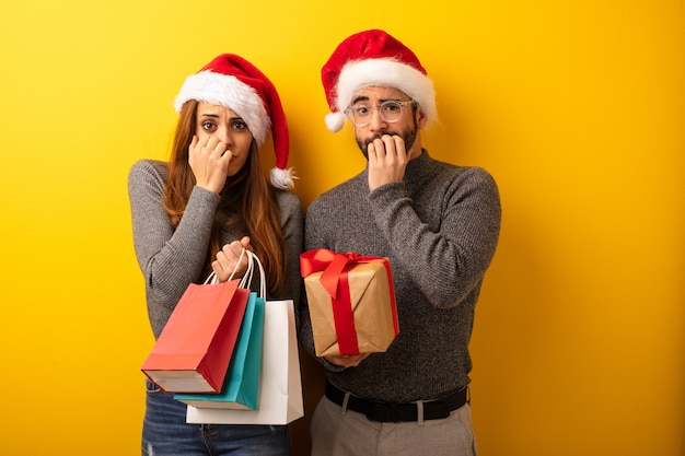Couple or friends holding gifts and shopping bags biting nails, nervous and very anxious