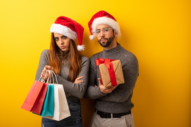Couple or friends holding gifts and shopping bags looking straight ahead