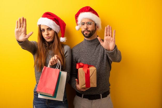 Couple or friends holding gifts and shopping bags putting hand in front