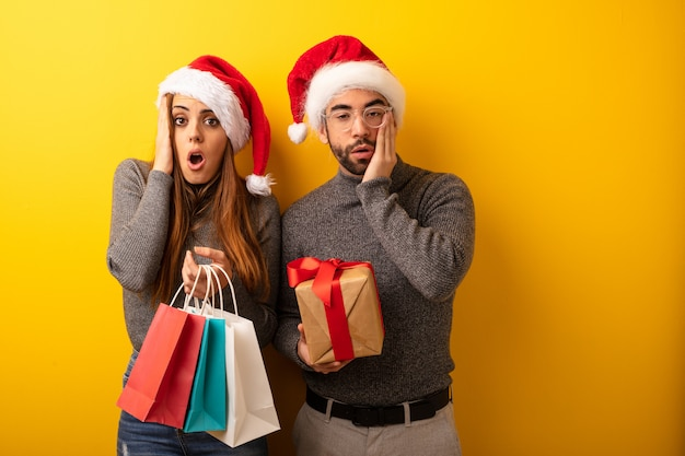 Couple or friends holding gifts and shopping bags surprised and shocked