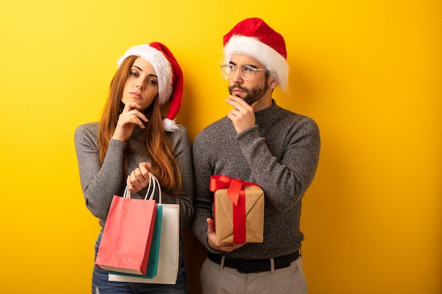 Couple or friends holding gifts and shopping bags thinking about an idea