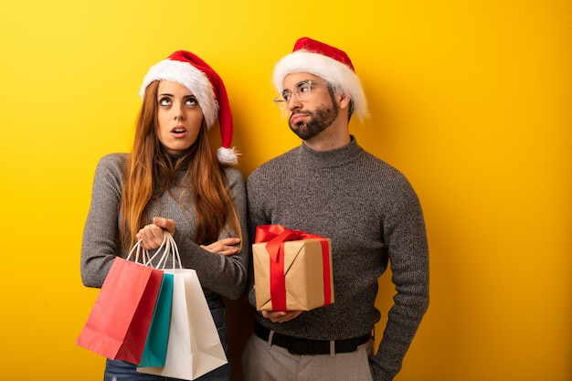Couple or friends holding gifts and shopping bags tired and bored