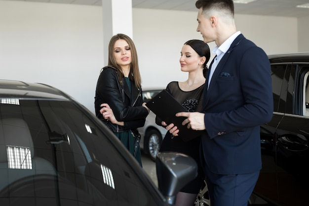 Couple of friends of womans with a car dealer choose a car in a car dealership