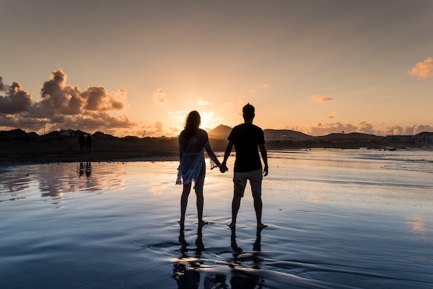 日没時にビーチで手をつないで後ろからカップル。