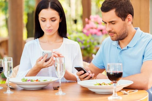 Пара из цифровой эпохи. молодая пара что-то набирает на своих смартфонах во время отдыха в ресторане на открытом воздухе вместе