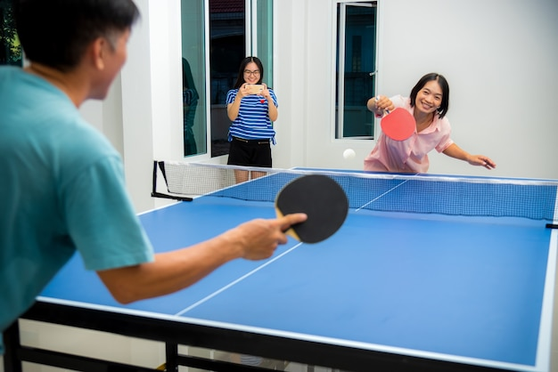 Пара развлекается, играя в настольный теннис или пинг-понг в помещении, вместе отдыхая и участвуя в спортивных играх дома. отец, мать и дочь азиатская семья наслаждается отдыхом, физическими упражнениями, оставаясь дома в таиланде