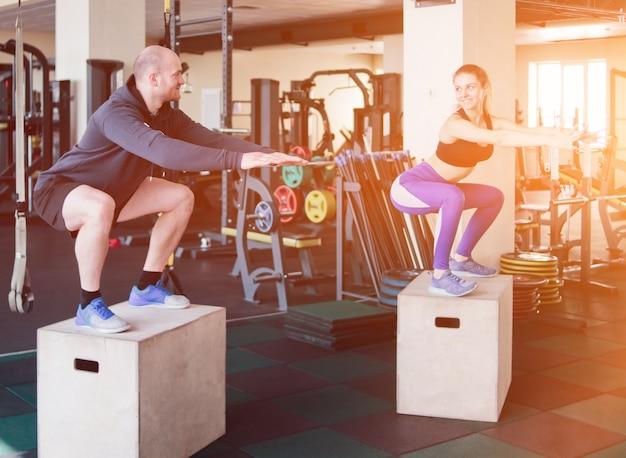 カップルのファンクショナルトレーニング。フィットネスの男性と女性がジムの木製の箱にジャンプします