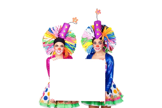 Couple of funny clowns with a blank poster isolated on white background