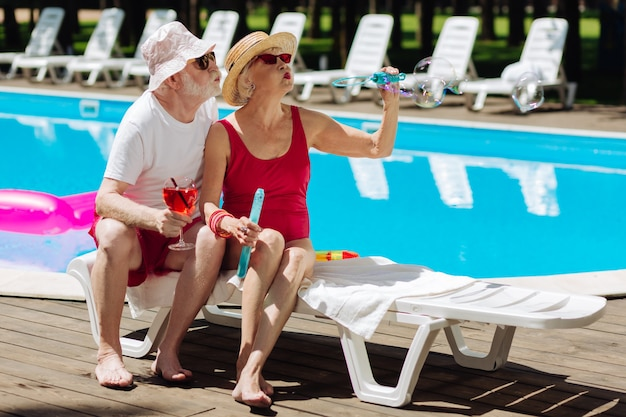 Couple of funny happy retired man and woman feeling relaxed while chilling under sun