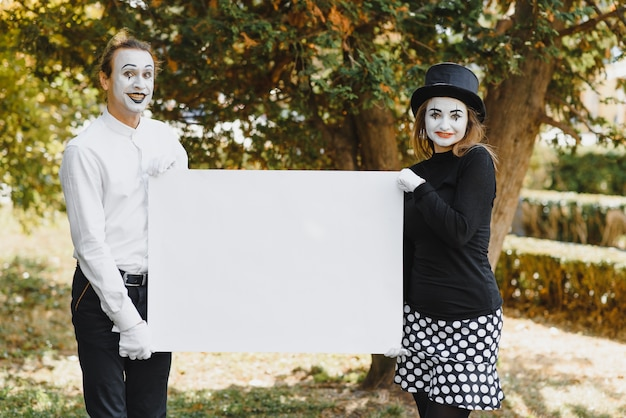Couple funny mimes holding sign
