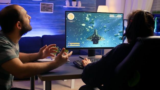 Coppia di giocatori che fanno il gesto del vincitore mentre giocano al campionato virtuale di sparatutto spaziale