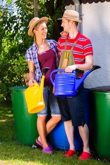 Couple in garden watering flowers
