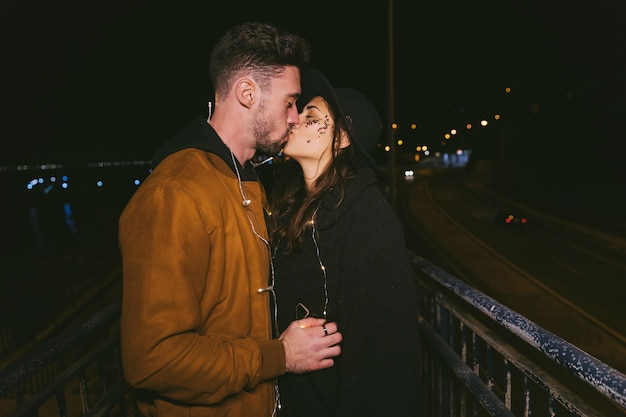 Couple in garland kissing in dark street