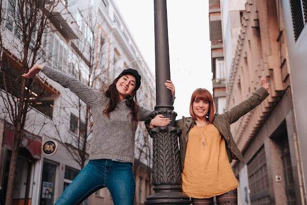 Couple of gay girls clinging to a lamppost happy