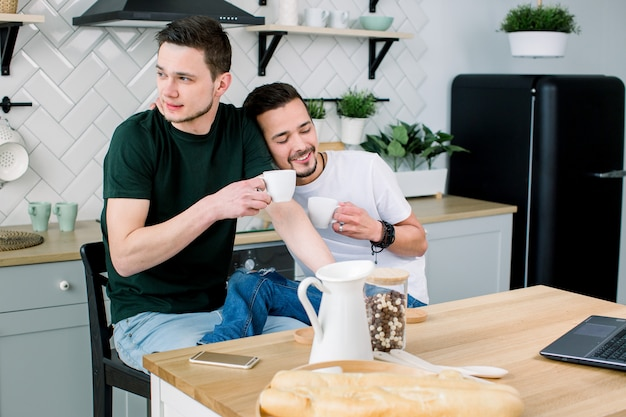Couple gay lgbt concept. couple love of smiley men drinking coffee or tea together in kitchen copy space. waking up with a coffee and kiss.