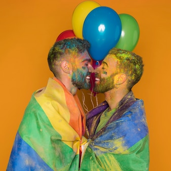 Couple of gently cuddling painted homosexual men with balloons