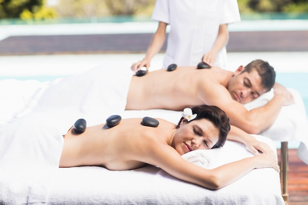 Couple getting a hot stone massage by the pool