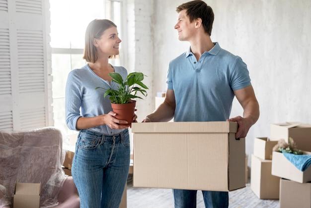 Пара собирает вещи в коробках, чтобы переехать