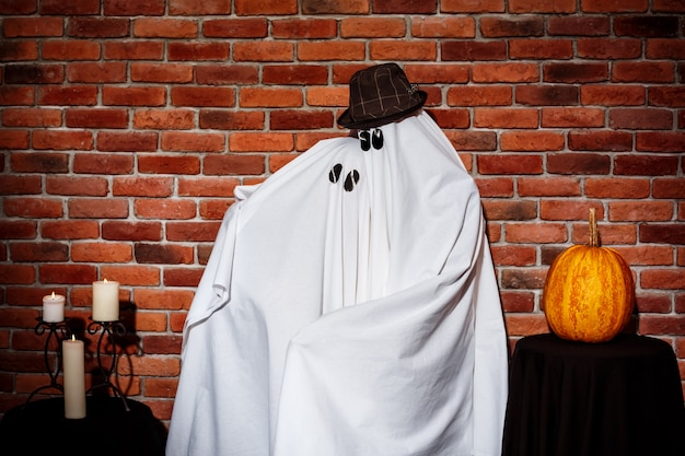 Couple of ghosts posing over brick wall. halloween party.