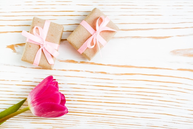 Couple of gift wrapped with pink ribbon and tulip on white wood, top view