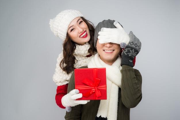 Подарок для пары. молодая женщина, дающая подарок парню на белом фоне