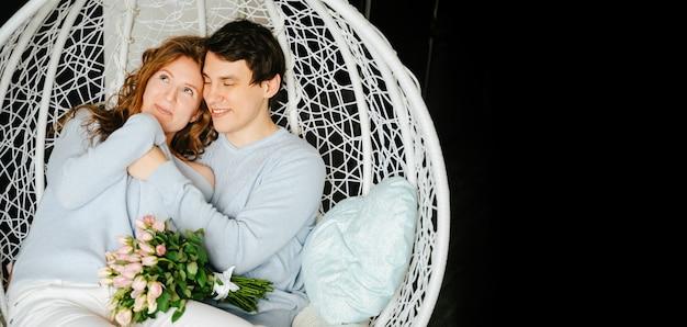 커플 소녀와 남자는 장미 꽃다발과 함께 큰 의자에 껴안고 있습니다. 흰색과 파란색 스웨터입니다.