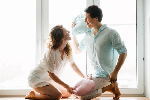 커플 여자와 남자는 창 근처 베개로 재생합니다. 흰색과 파란색 옷. 발렌타인 데이.