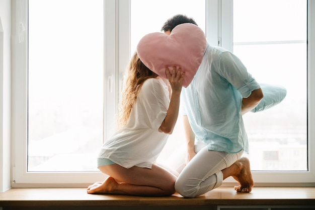 Couple girl and guy play with pillows near window. white and blue clothes. valentine day.