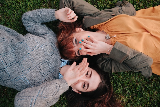 Couple of girls lying on the grass while laughing a lot