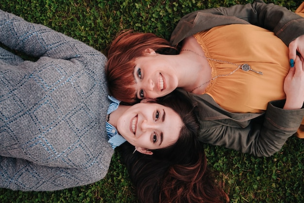 Couple of girls lying on the grass while looking at the camera