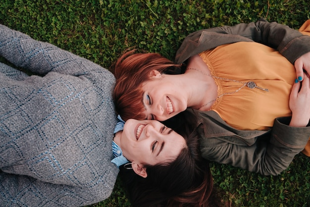 Couple of girls lying on the grass while looking at each other passionately