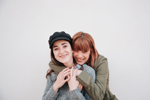Couple of girls in white background looking at the camera while they are happy