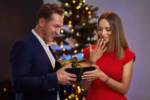 木の前でクリスマスプレゼントを贈るカップル。高品質の写真