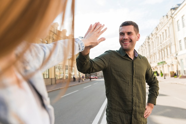 Couple giving high five on street