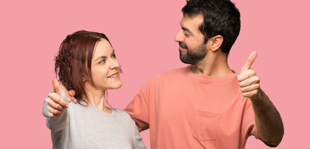 Couple giving a thumbs up gesture over isolated pink background