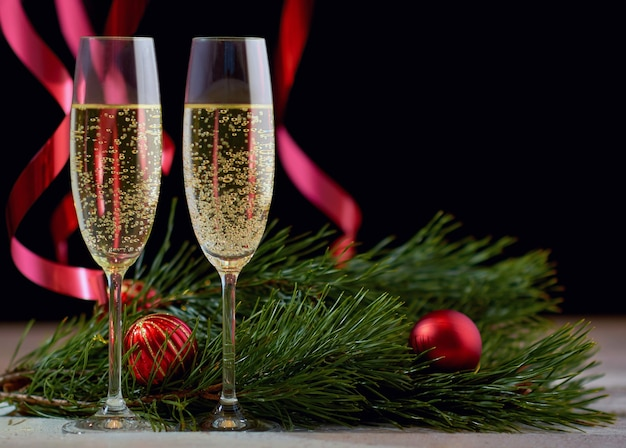 A couple of glasses with champagne on a wooden table with christmas gold balls, a red ribbon with a sprig of spruce