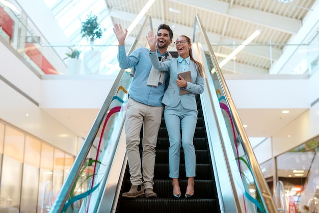 Пара спускается по эскалатору и машет своим друзьям. женщина держит планшет.