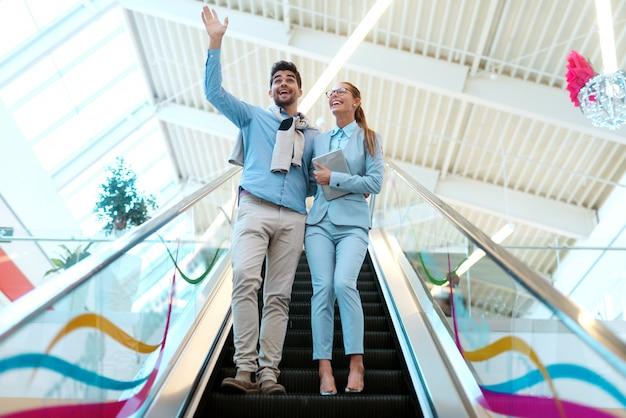 Пара, спускаясь по эскалатору в торговом центре. женщина, держащая таблетка, в то время как человек, махающий.