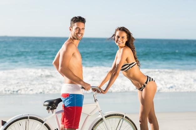 Пара, едущая на велосипеде по пляжу