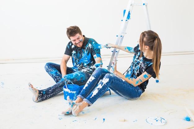 벽에 페인트를 칠하고 휴식 시간에 즐거운 시간을 보내는 커플