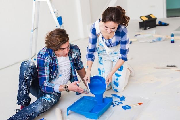 カップルが壁を塗るつもりで、彼らは色とブラシを準備しています。