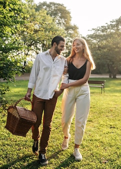 ピクニックをするために公園に行くカップル